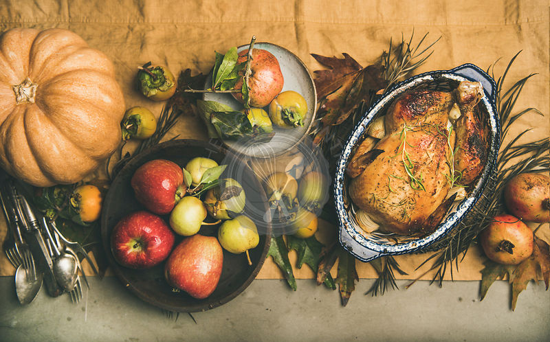 Thanksgiving dinner table setting with roasted meat, vegetables and fruit