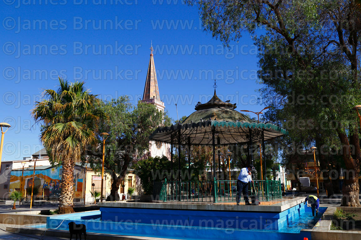 Bandstand and cleaners in Plaza 23 de Marzo, St John the Baptist cathedral in background, Calama, Region II, Chile