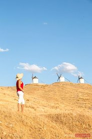 Tourist near windmills on the Don Quixote route, Spain