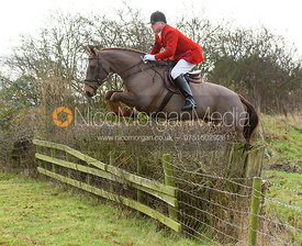 Michael Dungworth jumping a hedge near the meet - The Belvoir Hunt at The Wolds Farm 3/12