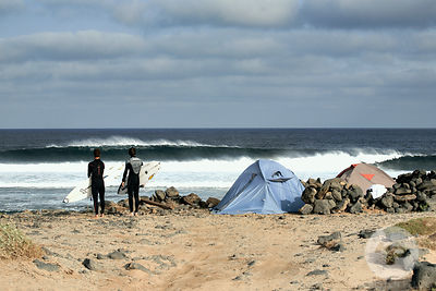 Two surfers watching a  wave breaking in front of a unauthorized campsite, La Graciosa island, Canary islands, Spain, march 2008.