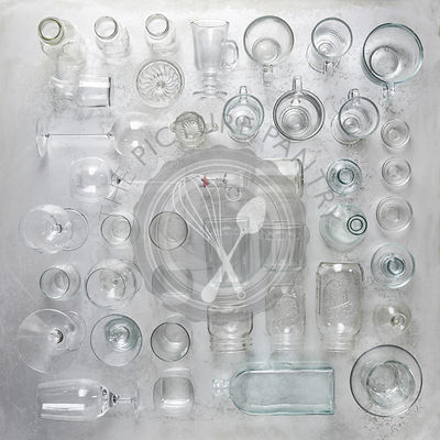 Collection of glassware laid out in a knolling fashion on rustic metal.