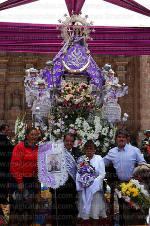 Hosting family (alferado) posing with statue of Virgen de la Candelaria after central mass, Puno, Peru