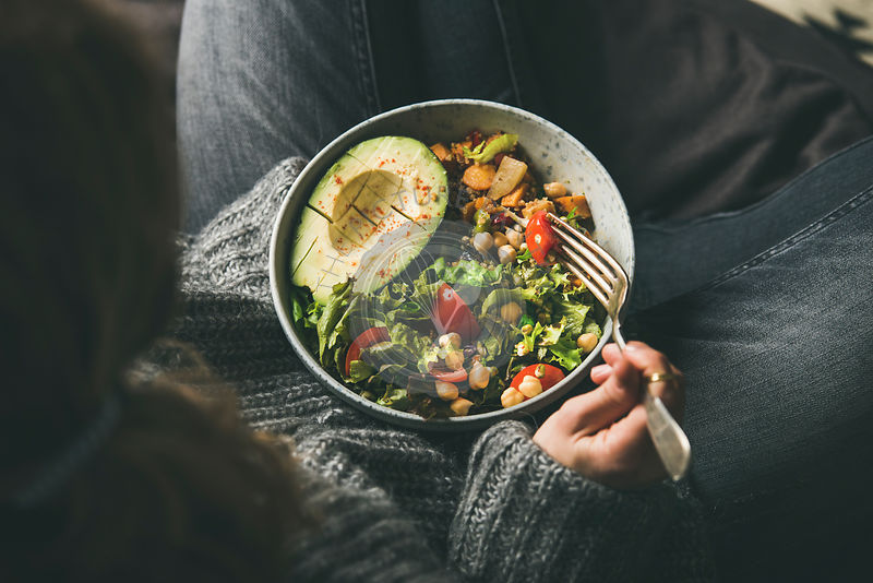 Woman holding bowl with healthy vegetarian dinner, top view