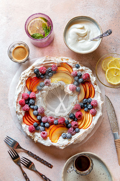 Pavlova wreath topped with fresh fruit on the table