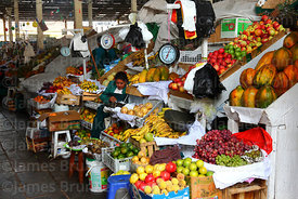 Woman selling fresh fruit on stall in San Pedro market, Cusco, Peru