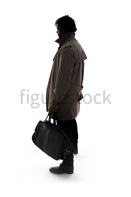 A Figurestock image of a man in a mac, standing, holding a black bag, in Silhouette – shot from eye level.