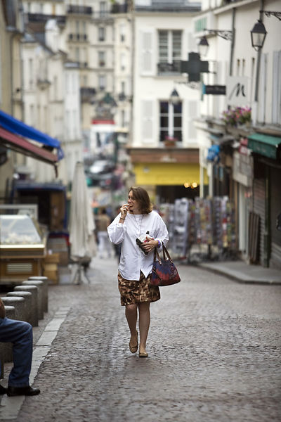 France - Paris - A woman eats fresh bread as she walks up the market in the Rue Mouffetard.