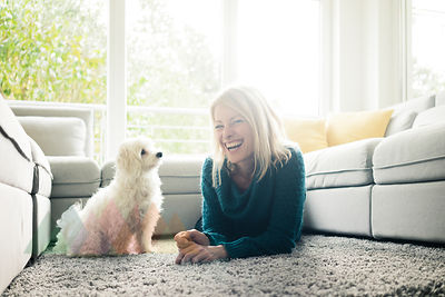 Happy woman with dog in living room