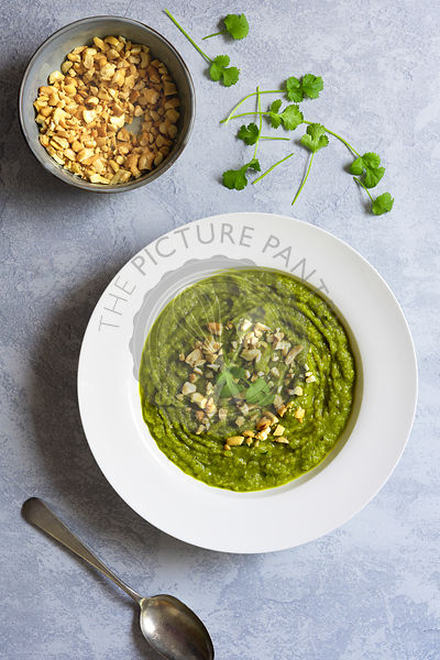 Broccoli soup garnished with cashew nuts and parsley.