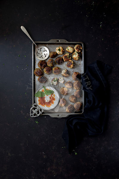 Greek Meatballs in a tomato sauce on a dark background