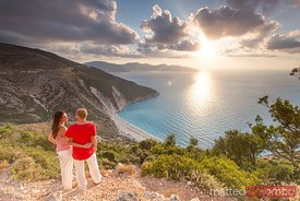 Couple enjoying sunset over famous Myrtos beach. Kefalonia, Greek Islands, Greece