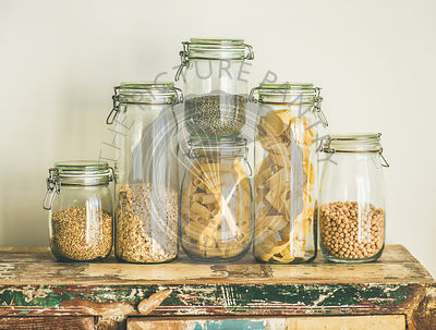 Various uncooked cereals, grains, beans and pasta for healthy cooking in glass jars on rustic wooden table