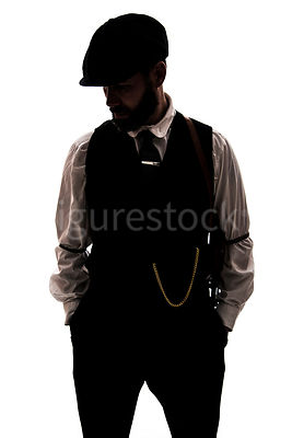 A silhouette of a vintage man in a peaky cap – shot from eye level.