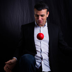 Ative corporate man portrait juggling with a red ball