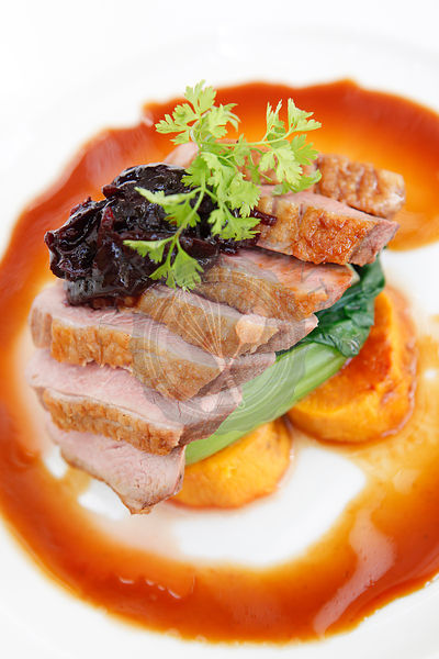 Roast duck breast on a bed of vegetables with cranberry sauce and gravy.