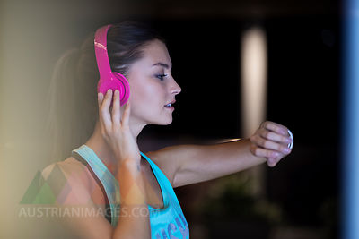 Young woman with pink headphones checking her smartwatch
