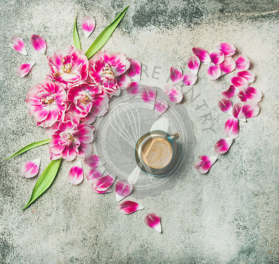 Flat-lay of cup of coffee surrounded with pink tulip flowers and petals in shape of heart over grey marble background