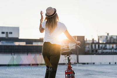Young woman pushing bicycle on parking level at sunset