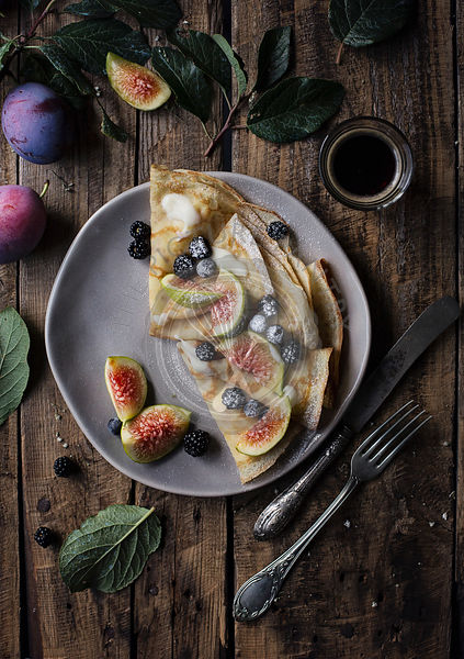 Crepes with figs and blackberries on wooden table. Top view