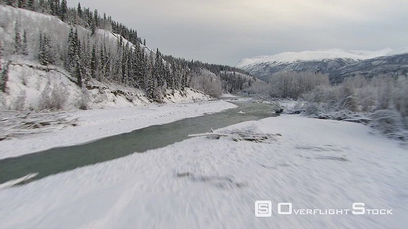Flying low along icy river's course in Alaska