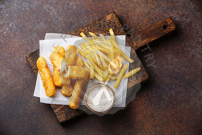 Fish fingers and Chips british fast food with tartar sauce on dark background