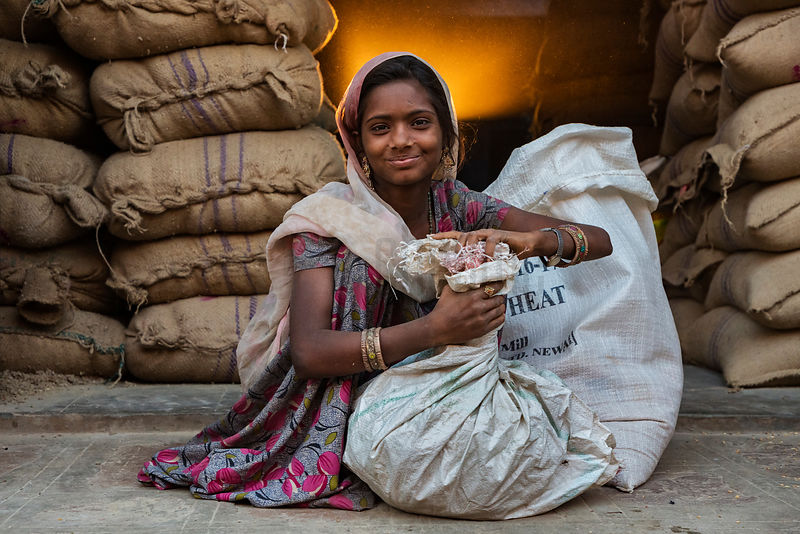 Young Woman Loading a Sack of Livestock Feed