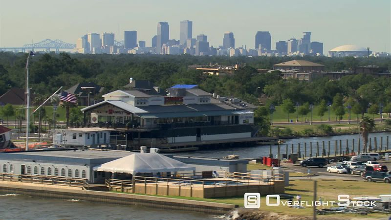 Hurricane Katrina damaged building along levee, with New Orleans, Louisiana skyline on horizon