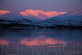 Sunrise on snow-capped mountains and fjord