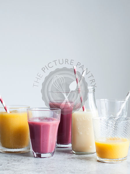 Fruit smoothies in mismatched glasses and bottles with paper straws