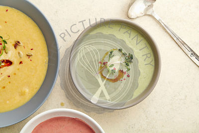 Three bowls with colorful vegetarian creamy soups with broccoli, pumpkin and beetroot