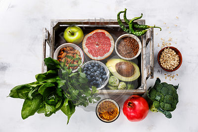 Healthy food clean eating selection in wooden box: fruit, vegetable, seeds, superfood, cereals, leaf vegetable on white background