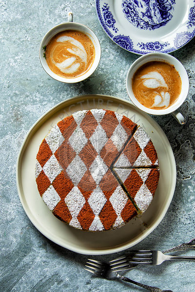 Sponge cake decorated with cocoa powder and icing sugar on a plate and two cups of coffee on the table