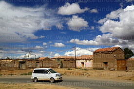Car passing adobe / mud brick houses in Belén village, Potosí Department, Bolivia