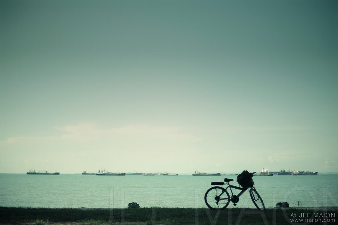 Bicycle by sea and cargo boats