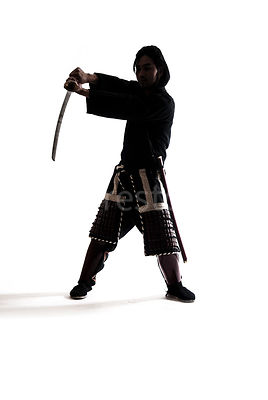 A silhouette of a Samurai warrior with his sword in the air - shot from mid-level.