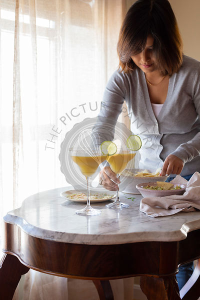 Woman placing a Mango Margarita on a table, along with dips