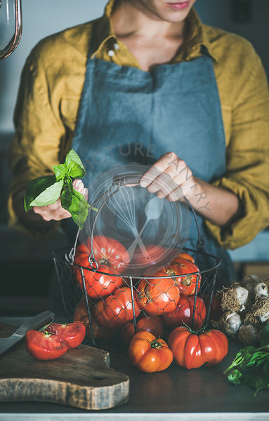Woman in apron holding basket with heirloom tomatoes for cooking
