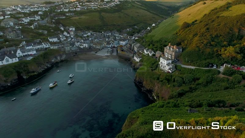 Drone flies sideways from cliffs with the village of Port Isaac behind during morning twilight.