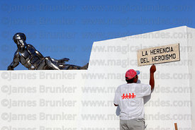 Man cleaning monument at site of Battle of Alto de la Alianza for 26th May anniversary events, near Tacna , Peru