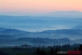 Mist filled landscape at dawn, with farmhouse, Tuscany, Italy