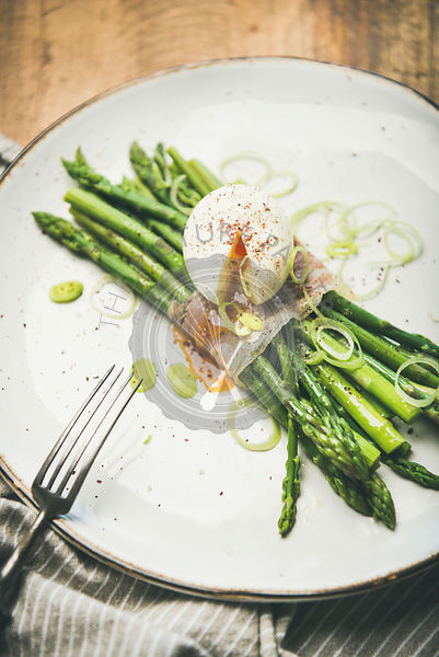 Green asparagus with soft-boiled egg in white plate, selective focus