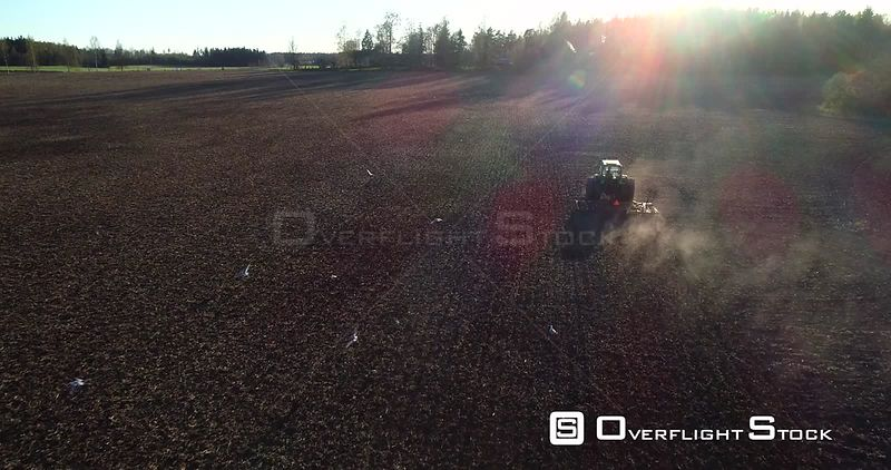 Spring Tractor, Aerial View of a Plow Machine Plowing and Segull Birds Flying Around the Vechicle, Sunny Spring Evening Dawn, Uusimaa, South Finland