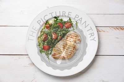 Roasted grilled chicken breast and fresh salad with tomato and arugula on wooden background