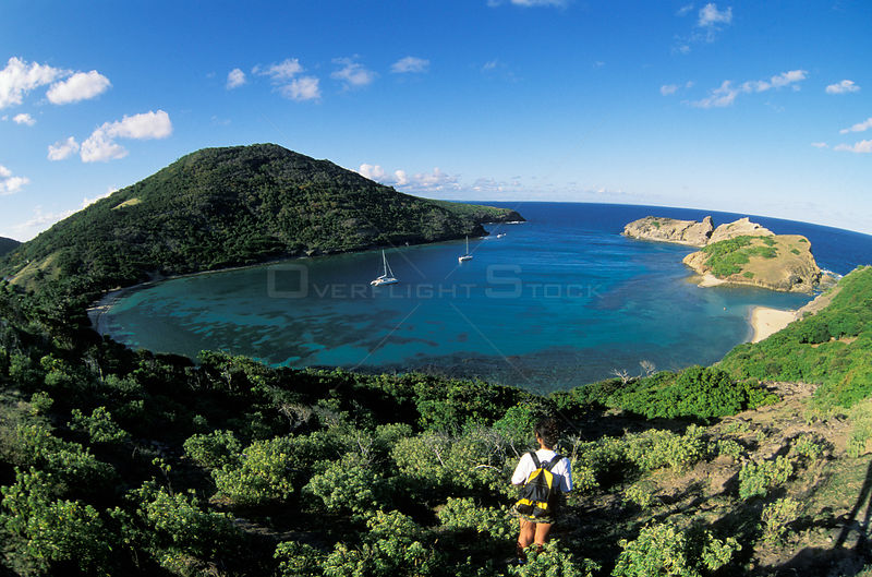 Woman looking out over yachts moored in a bay. Les Saintes island, Caribbean.