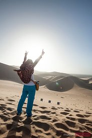 Young chinese woman exulting  on top of sand dunes desert