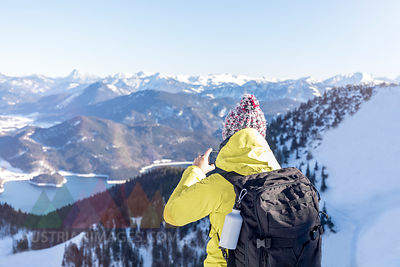 Germany, Bavaria, Alps, hiker with backpack at Lake Walchen taking smartphone picture