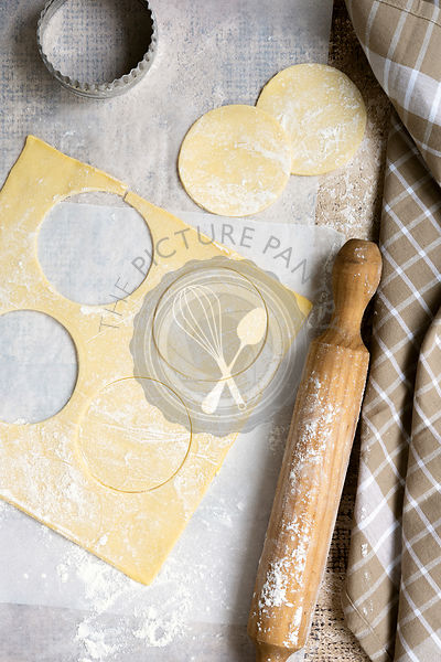 Round circles of shortcrust pastry cut from a sheet and a rolling pin and a biscuit cutter along side.