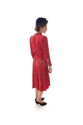 A 1940's woman in a red dress and a hat – shot from eye-level.