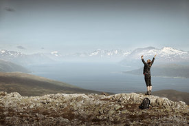 Woman standing with stretched arms above fjord scenery